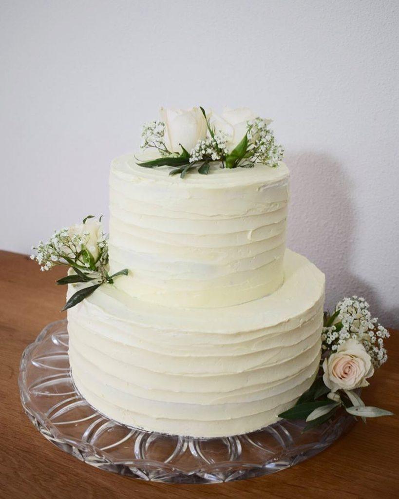 Bruidstaart met creme, witte rozen en gipskruid