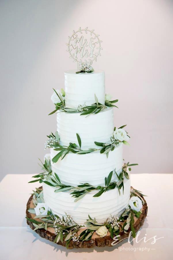 Bruidstaart met olijftakken op houten schijf