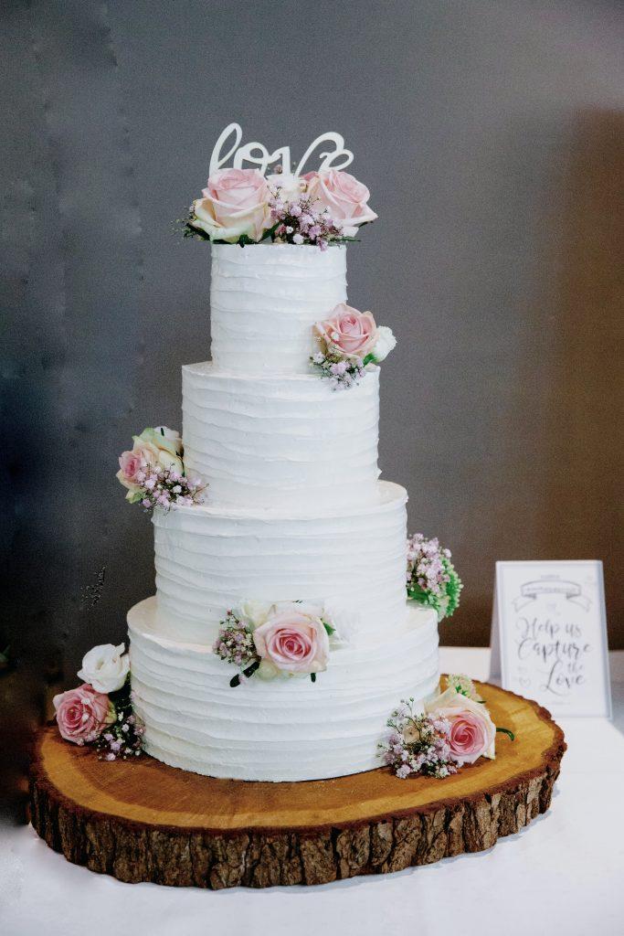 Bruidstaart met roze rozen en gipskruid